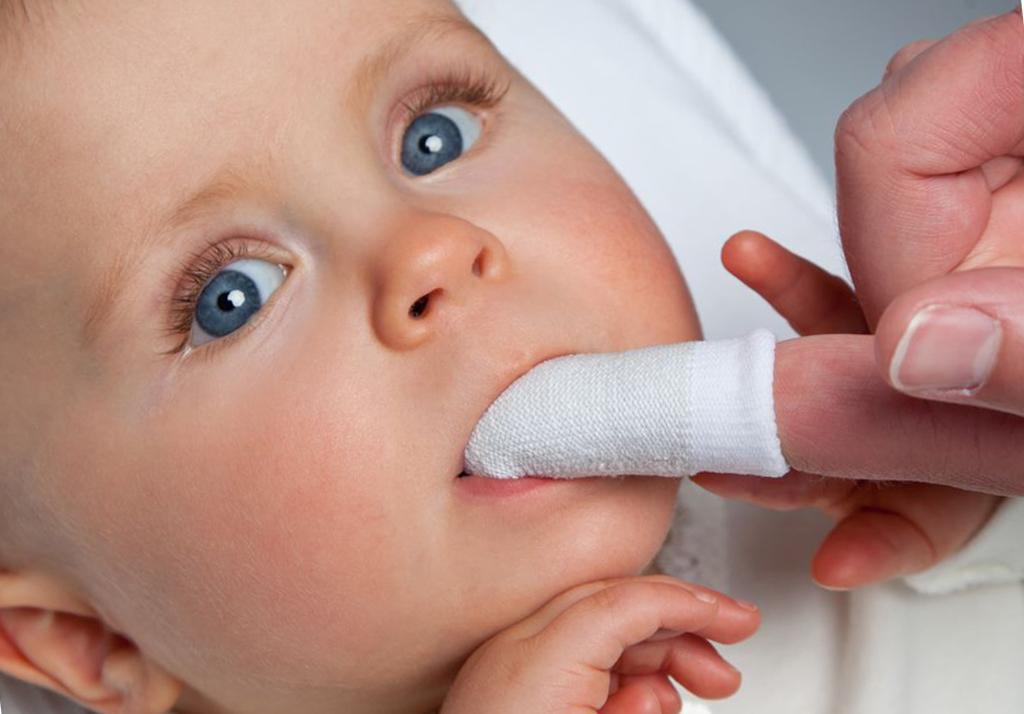 На фото показана гигиена полости рта у младенца с помощью специальной салфетки