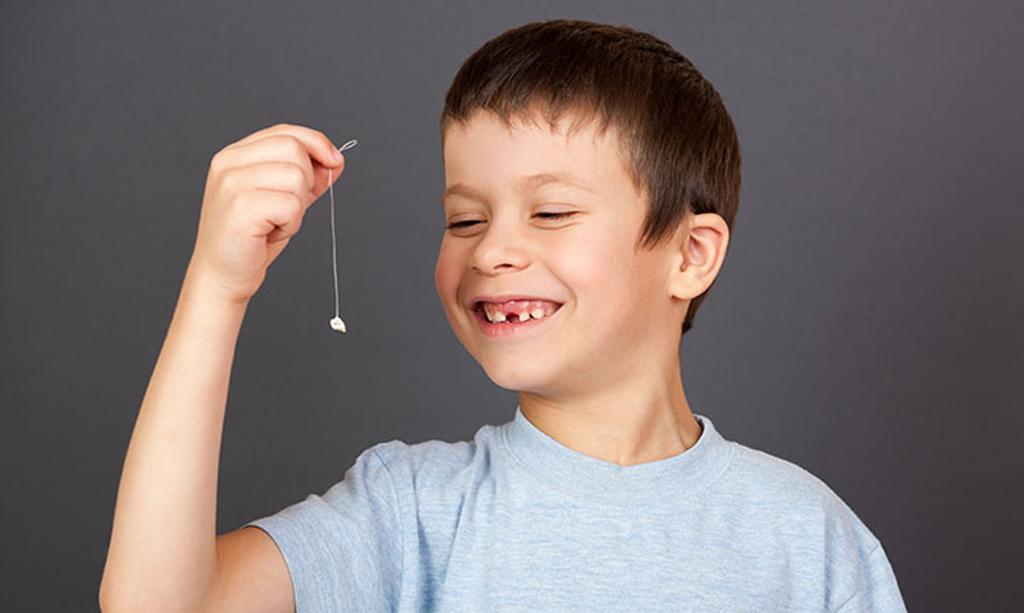 Можно удалить молочный зуб самостоятельно с помощью нити