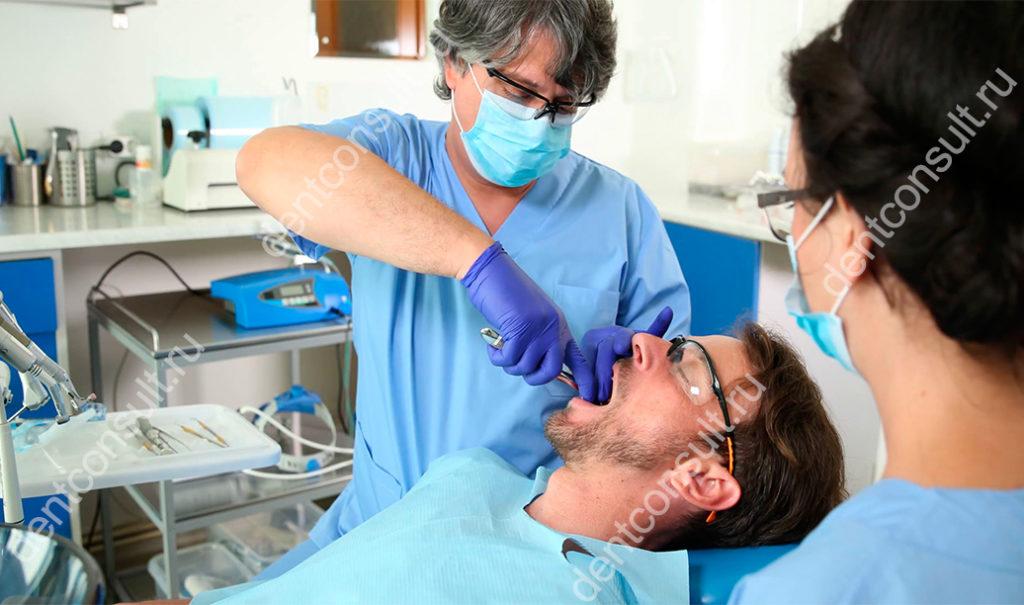 вырывает зуб